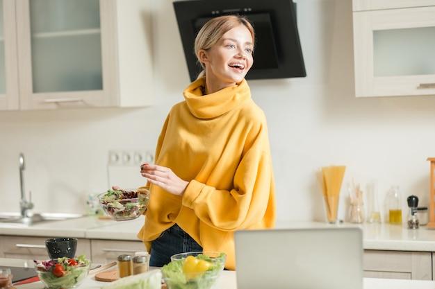 Heureuse jeune femme se sentir excitée et regarder ailleurs avec un sourire tout en étant dans la cuisine avec un bol de salade dans ses mains