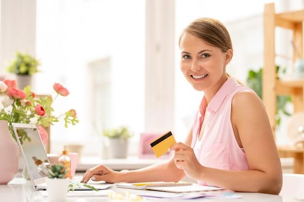 Heureuse jeune femme séduisante avec carte en plastique vous regarde lors de la commande en ligne au bureau