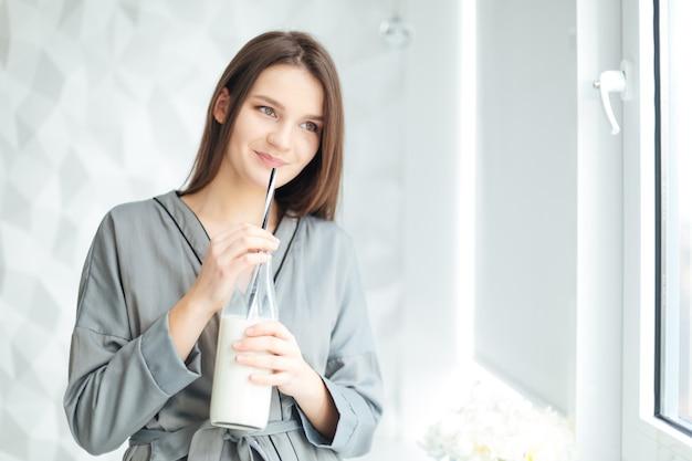 Heureuse jeune femme séduisante debout près de la fenêtre et boire du lait