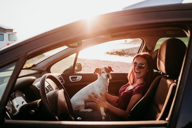 Heureuse jeune femme et son mignon chien jack russell dans une voiture au coucher du soleil. concept de voyage