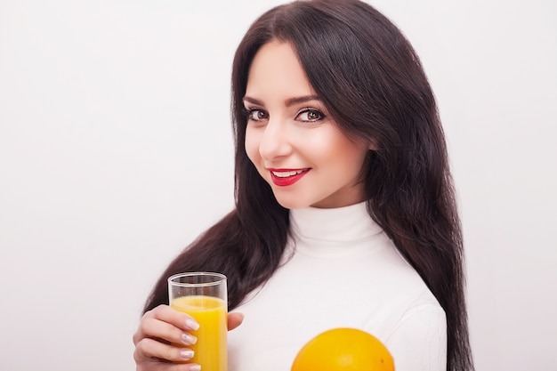 Heureuse jeune femme souriante, boire du jus d'orange