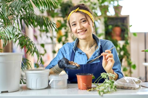 Heureuse jeune femme souriante à la caméra versant le drainage dans un pot de fleurs tout en se préparant à planter