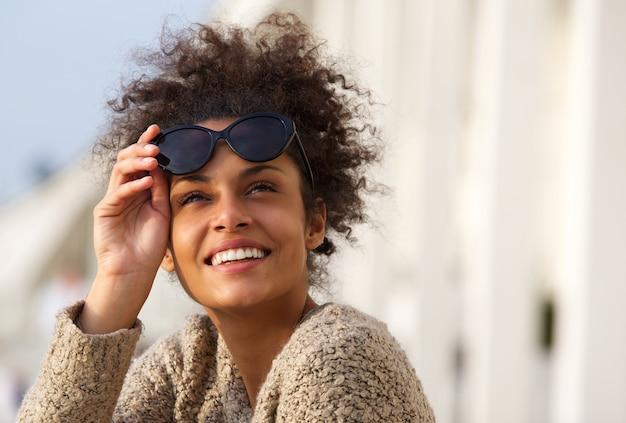 Heureuse jeune femme souriante à l'extérieur