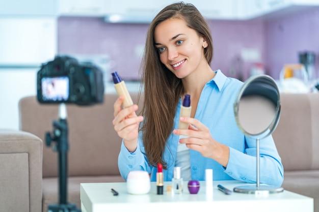 Heureuse jeune femme souriante influenceuse blogueuse vidéo tenant une fondation lors de l'enregistrement de son blog beauté, maquillage et cosmétiques à la maison.