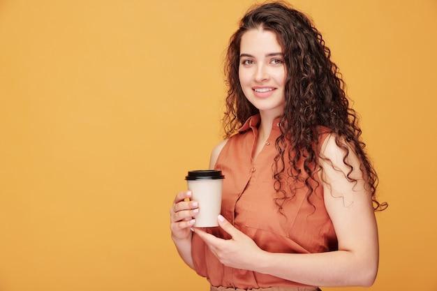 Heureuse jeune femme souriante avec de longs cheveux ondulés noirs tenant un verre de café en position debout avec fond sur la gauche