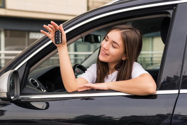 Heureuse jeune femme souriante avec une nouvelle clé de voiture