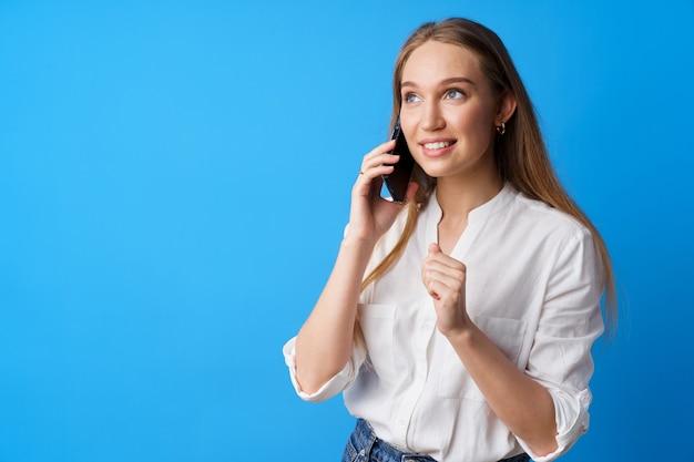 Heureuse jeune femme souriante parlant au téléphone sur fond bleu