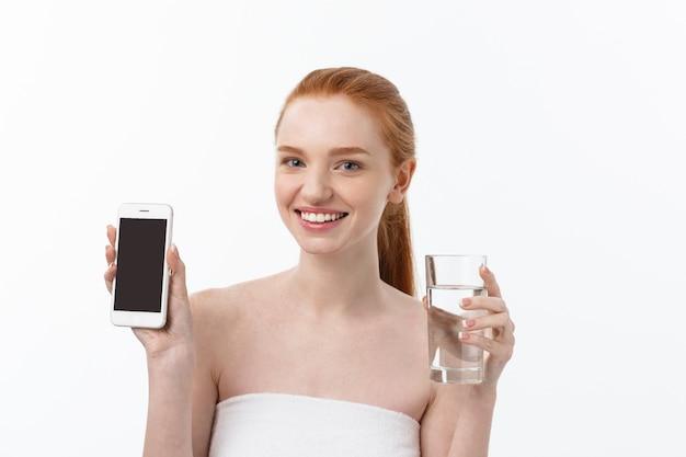 Heureuse jeune femme souriante avec une peau saine, lecture et écriture sur mobile