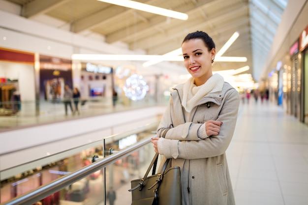 Heureuse jeune femme souriante posant dans un centre commercial