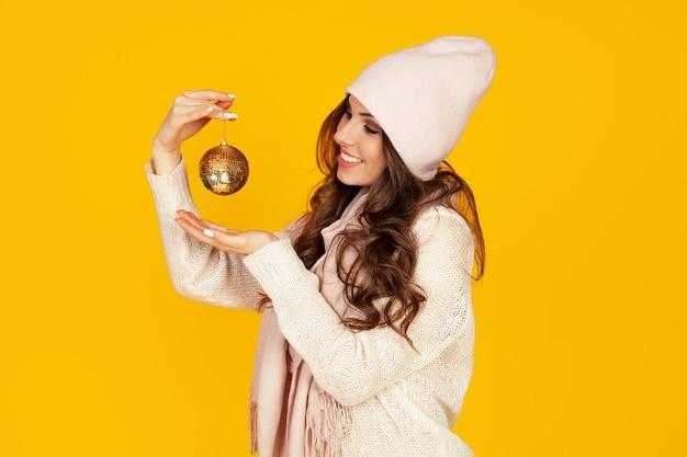 Heureuse jeune femme souriante tenant une boule de sapin de noël