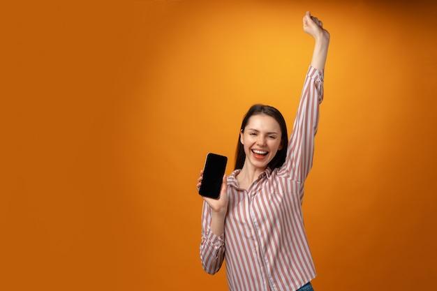 Heureuse jeune femme souriante vous montrant un écran de smartphone noir avec espace de copie
