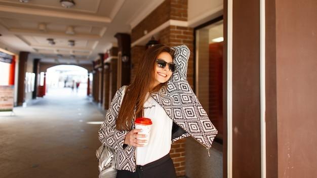 Heureuse jeune femme avec un sourire marchant avec du café dans la ville et profitant d'une journée ensoleillée