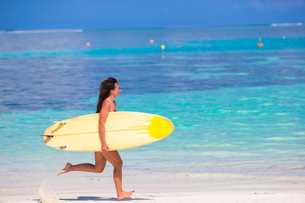 Heureuse jeune femme surf sur la plage avec une planche de surf