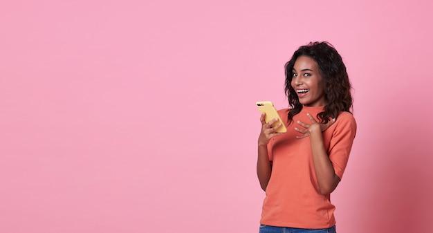Heureuse jeune femme surprise après avoir lu le message du smartphone isolé sur rose