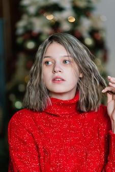 Heureuse jeune femme surprise émotionnelle par un arbre de noël dans un salon confortable, concept de bonheur
