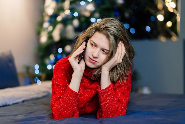 Heureuse jeune femme surprise émotionnelle par l'arbre de noël dans un salon confortable, concept de bonheur