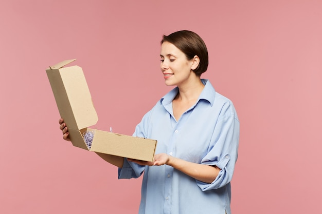 Heureuse jeune femme surprise ouvrant la boîte et regardant le cadeau