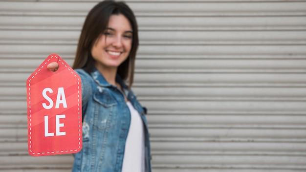 Heureuse jeune femme avec tablette de vente près du mur de tôle profilée