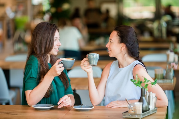 Heureuse jeune femme avec une tasse de café au café en plein air. concept de communication et d'amitié