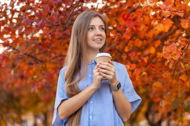 Heureuse jeune femme avec une tasse de café pour aller sur les arbres rouges d'automne