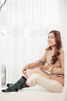 Heureuse jeune femme avec une tasse de café ou de thé sur le rebord de la fenêtre