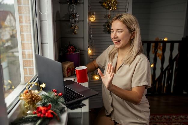 Heureuse jeune femme avec une tasse de café en utilisant le zoom pour féliciter joyeux noël ses proches. faire des appels vidéo facetime avec un ordinateur portable à la maison.