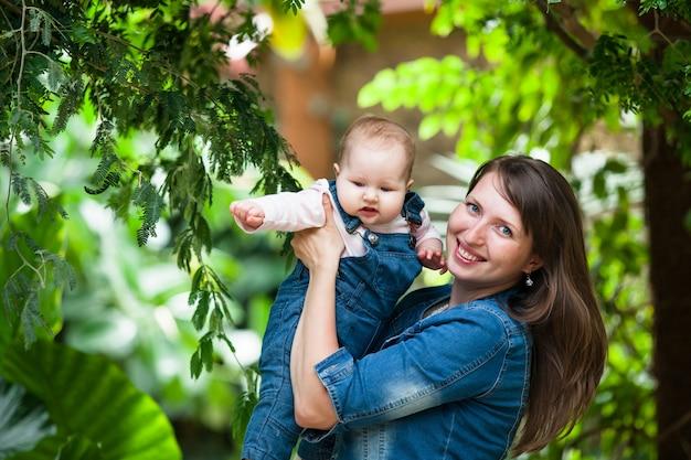Heureuse jeune femme tenant un bébé à pied dans le parc