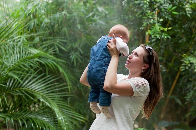 Heureuse jeune femme tenant un bébé sur une promenade dans le parc