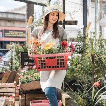 Heureuse jeune femme tenant un conteneur avec de belles fleurs