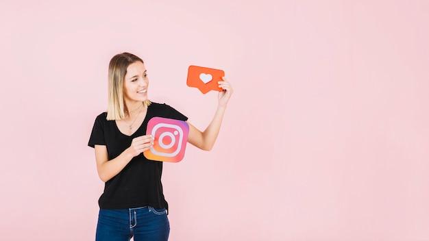 Heureuse jeune femme tenant l'icône de l'amour et instagram