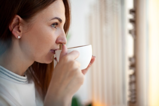 Heureuse jeune femme tenant avec les mains une tasse de café au lait chaud sain