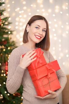 Heureuse jeune femme tenant de nombreuses boîtes présentes avec arbre de noël et lumières