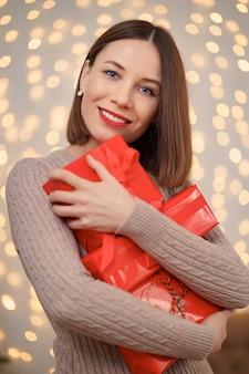 Heureuse jeune femme tenant de nombreuses boîtes présentes avec des lumières