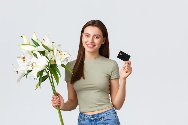Heureuse jeune femme tendre a commandé la livraison d'un bouquet de fleurs avec carte de crédit souriante heureuse et ho...