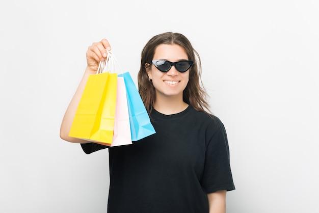 Heureuse jeune femme tient des sacs à provisions sur fond blanc.
