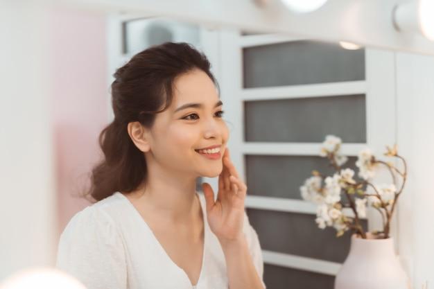 Heureuse jeune femme touchant son visage avec les mains, se reflétant dans le miroir.