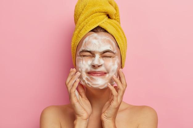 Heureuse jeune femme touche la peau du visage avec du savon, garde les yeux fermés, se lave le visage le matin, se tient nue contre un mur rose, reçoit un soin spa. concept de propreté