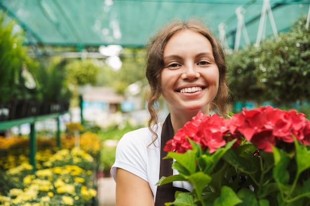 Heureuse jeune femme travaillant dans une serre