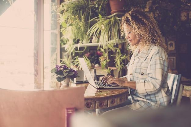 Heureuse jeune femme travaillant et tapant sur un ordinateur portable assis sur une chaise. femme d'affaires travaillant à domicile. indépendante occupée à travailler ou à taper sur un ordinateur portable au bureau à domicile