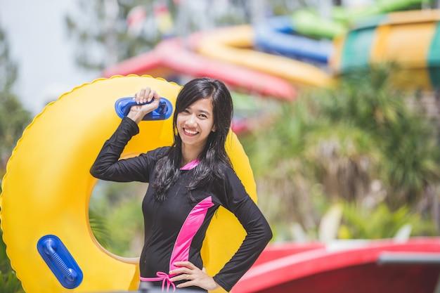 Heureuse jeune femme avec tube dans un parc aquatique resort