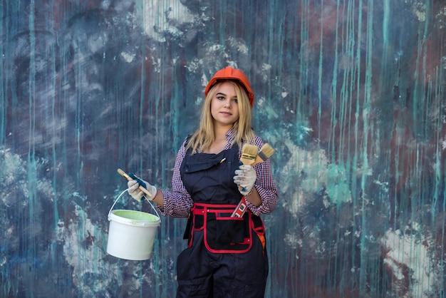 Heureuse jeune femme en uniforme tenant un rouleau à peinture près du mur de couleur. concept de décoration à la maison
