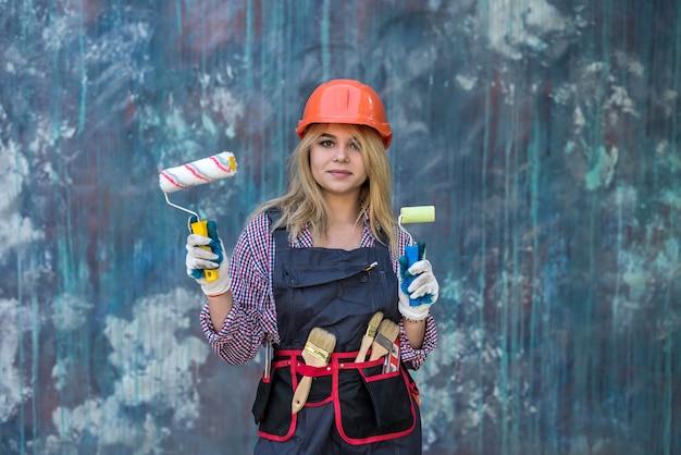 Heureuse jeune femme en uniforme tenant le rouleau à peinture près du mur de couleur. concept de décoration de la maison