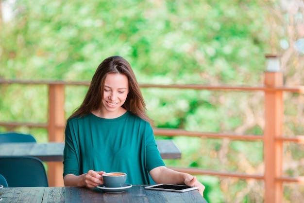 Heureuse jeune femme urbaine, boire du café au café