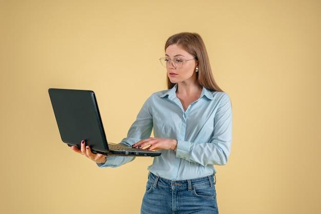 Heureuse jeune femme utilisant un ordinateur portable, portant des lunettes sur fond jaune