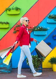 Heureuse jeune femme va avec des sacs près du mur