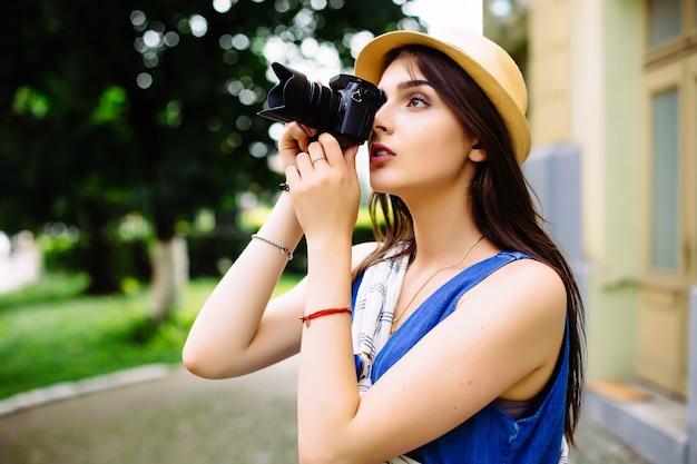 Heureuse jeune femme en vacances photographier avec appareil photo dans la rue de la ville