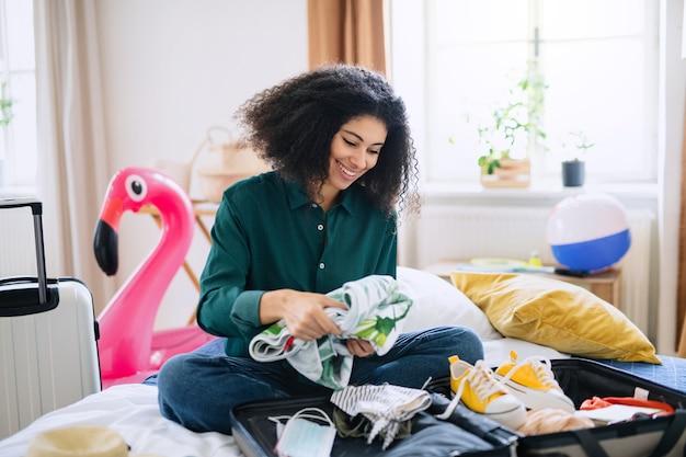 Heureuse jeune femme avec valise d'emballage pour des vacances à la maison, concept de coronavirus.