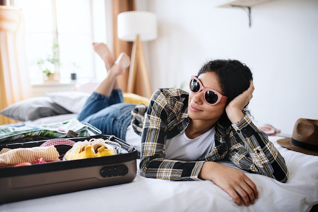 Heureuse jeune femme avec valise et lunettes de soleil emballage pour des vacances à la maison.