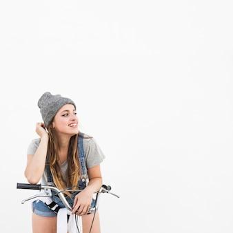 Heureuse jeune femme à vélo jaune en détournant les yeux