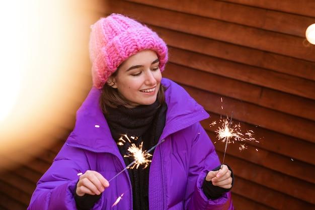 Heureuse jeune femme en vêtements d'extérieur avec des cierges magiques dans la rue sur le fond d'un mur en bois se réjouit...
